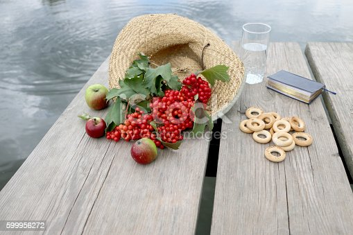 845307398 istock photo Red berries viburnum on a  table in a straw hat 599956272