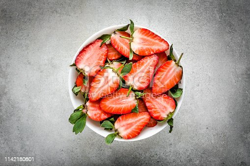 640978994 istock photo Red berry. Fresh pieces of strawberry in a bowl, top view. 1142180801