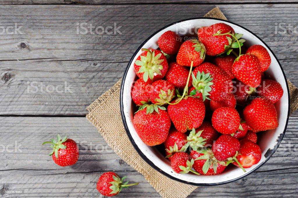 Red berry Erdbeere in Metall Becher auf rustikalen hölzernen Hintergrund. Direkt von oben. Ansicht von oben. – Foto