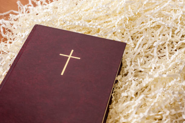 Red Bible with gold cross laying on paper filling. stock photo