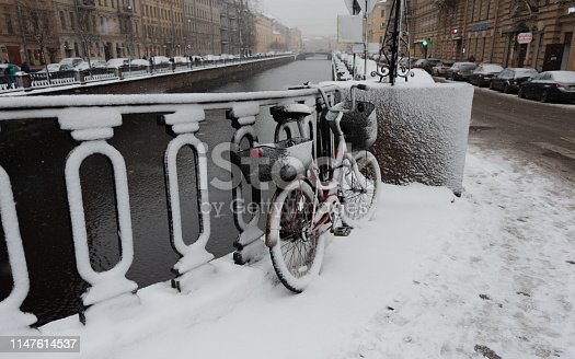Red bicycle with baskets covered with snow leaning against a fence next to Griboyedov Canal at snowing winter day