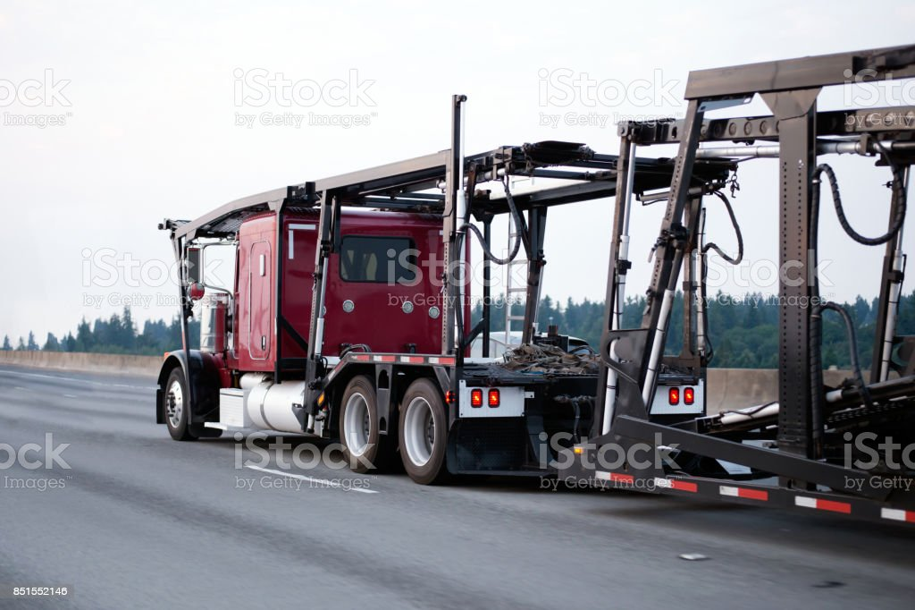 Red big rig classic semi truck car hauler with empty trailer running on highway stock photo