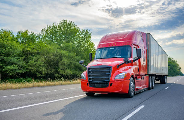 Red big rig long haul semi truck with black grille transporting cargo in dry van semi trailer running on the wide highway road stock photo