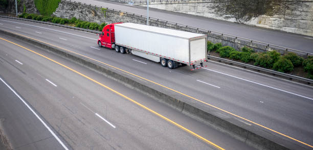 Red big rig long haul semi truck with dry van semi trailer running on divided wide highway stock photo