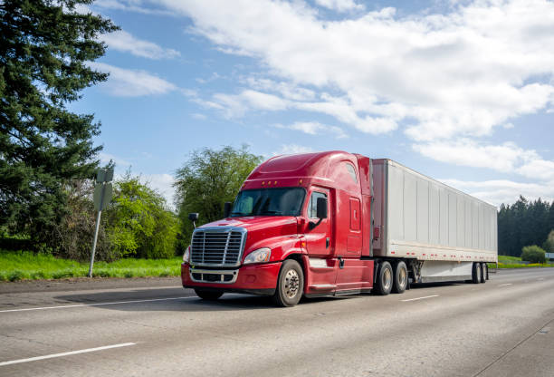 Red big rig popular bonnet semi truck transporting commercial cargo in dry van semi trailer moving on the straight wide highway stock photo