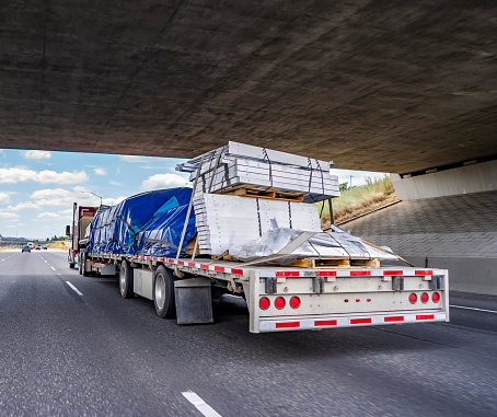Hard loaded classic red big rig semi truck transporting covered and tightened commercial cargo on flat bed semi trailer running under the bridge across wide multiline highway road for delivery