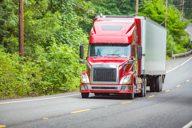 Red big rig semi truck with refrigerator semi trailer climbing uphill on the winding forest road  with green trees stock photo