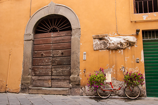 Red bike full of flowers standing in front medieval door