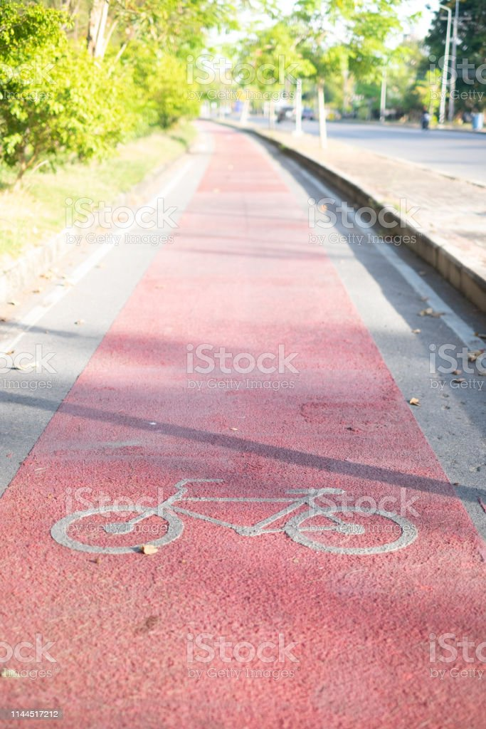 Red Bike lane asphalt texture with sunlight in background in the...