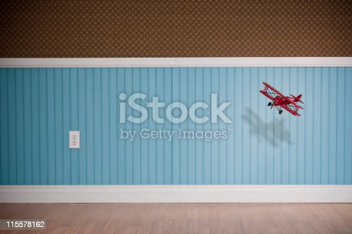 Red biplane flying in empty room. The wall has a blue beadboard wainscoting and a patterned wallpaper.*