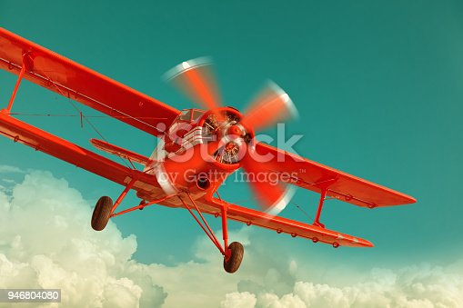 istock Red biplane flying in the cloudy sky 946804080