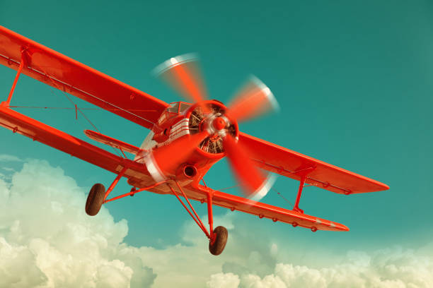 Red biplane flying in the cloudy sky stock photo