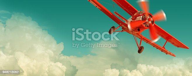 Red biplane flying in the cloudy sky. Retro style