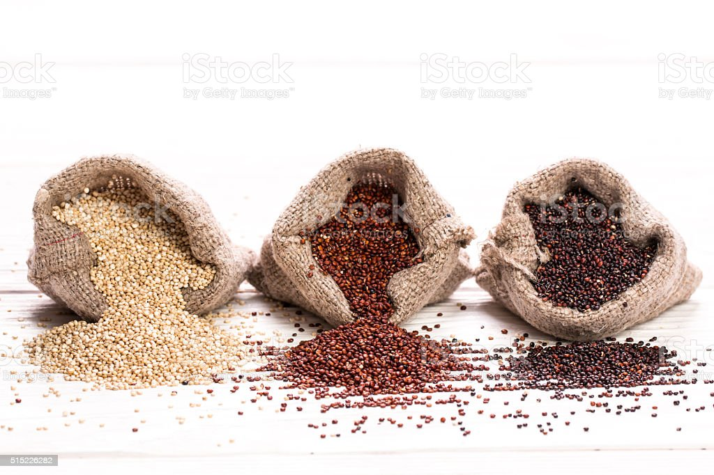 Red, black and white quinoa seeds on a wooden background stock photo