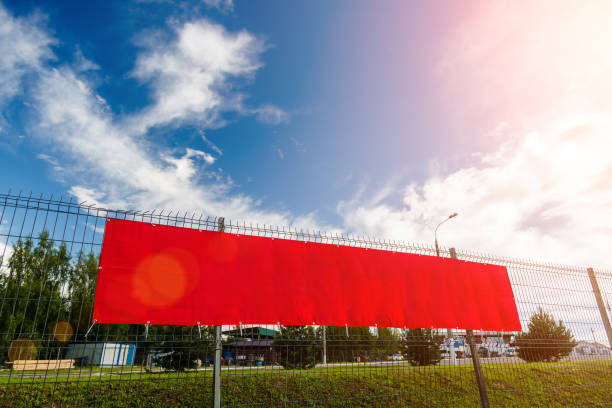 Red blank advertising banner hanging on a fence against the blue sky on a sunny day. stock photo