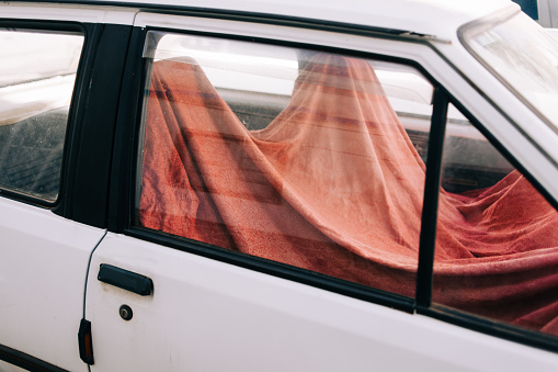 Red blanket over seats of an old car