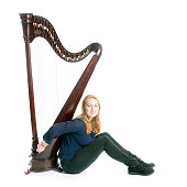 red blond caucasian teenage girl with harp sits on floor against white studio background