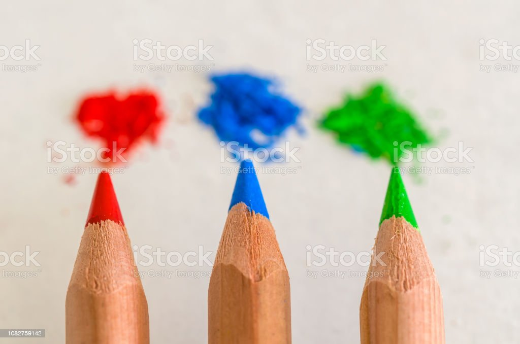 Red, blue and green colored pencils and powders. stock photo