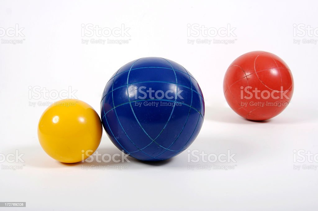 Red, Blue, and Yellow Bocce Balls of varying sizes stock photo