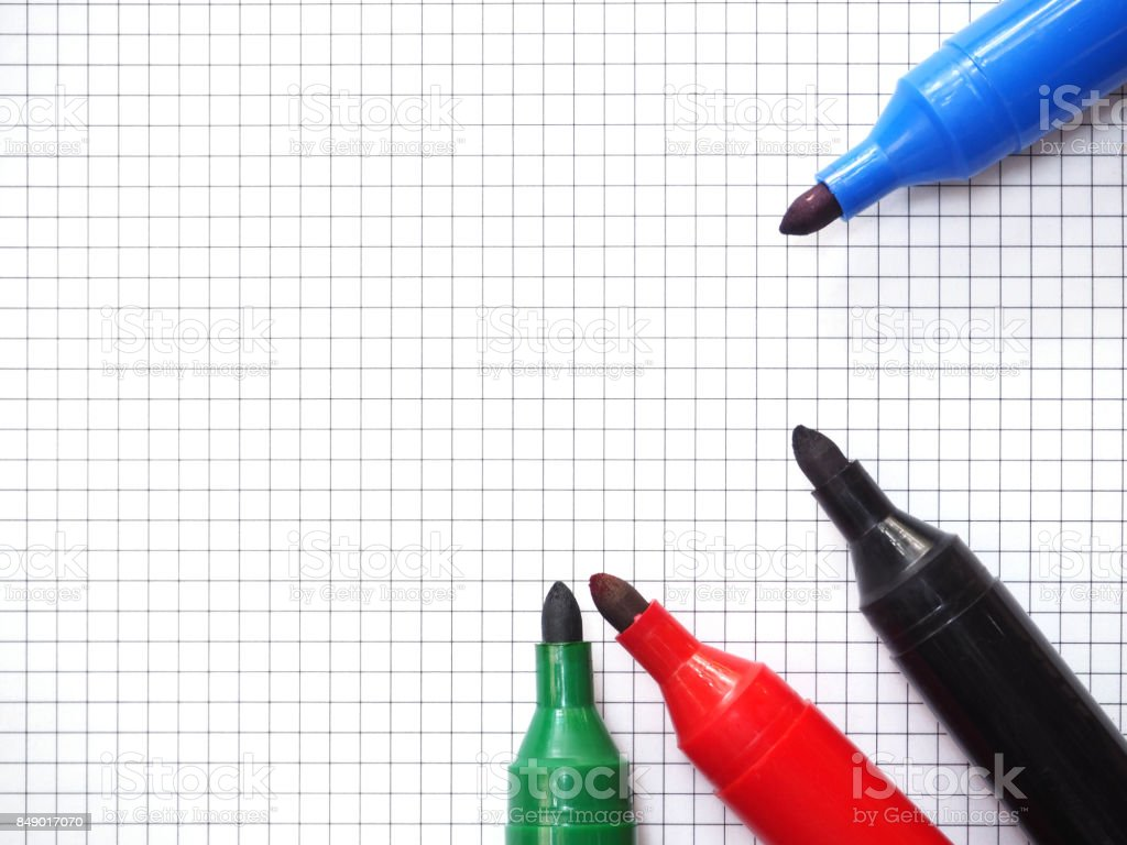 Red Blue Black And Green Marker Pens On Blank Graph Paper Sheet