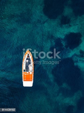 istock Red boat in deep blue water. Aerial view 914429152