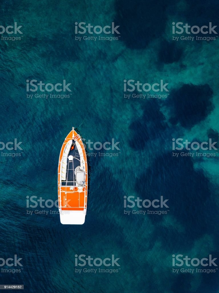 Red boat in deep blue water. Aerial view stock photo