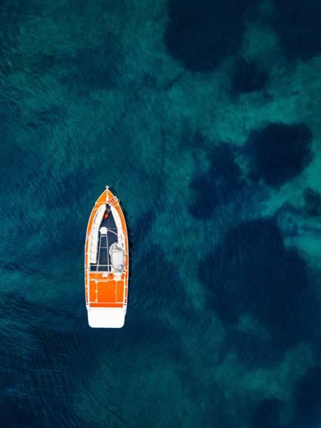 röd båt i djupblå vatten. flygfoto - vattenlandskap bildbanksfoton och bilder