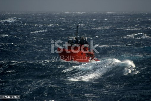 small ship sailing in large waves in a north sea winter storm. Boat is showing rolling motion against horizon in very bad weather. Ship is an oil industry rig support vessel used for offshore safety. Highlights shipping and dangers of sailing and transportation in bad weather and the bravery of the people who do this as a career.