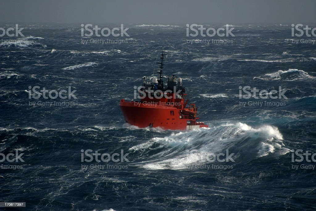 Red boat in the sea during a storm stock photo