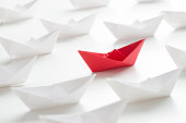 Red paper boat among many white paper boats on white background.