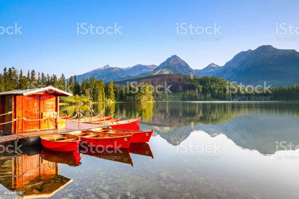 Red boats moored at wooden house on a lake with a clear  water against the background of high mountains.Strbske Pleso lake, Slovakia, Tatra mountains. stock photo