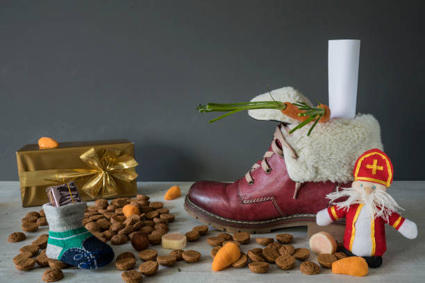 red boot with wish list and carrots, ginger nuts, for traditional Dutch event Sinterklaas Sinterklaas event scene, with traditional candy. The Netherlands and Belgium sinterklaas stock pictures, royalty-free photos & images