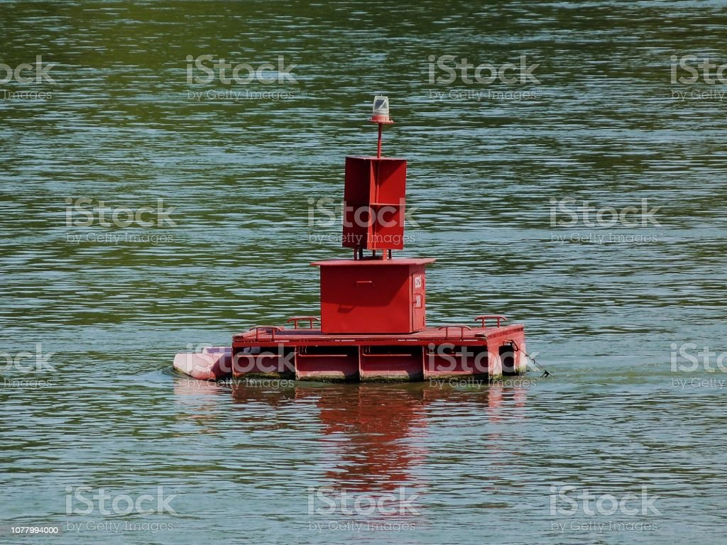 red bouy in green river on calm waters on summer day stock photo