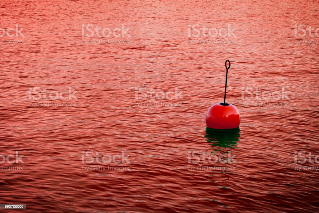 Red bouy on a calm bloody lake - concept image with copy space'n stock photo