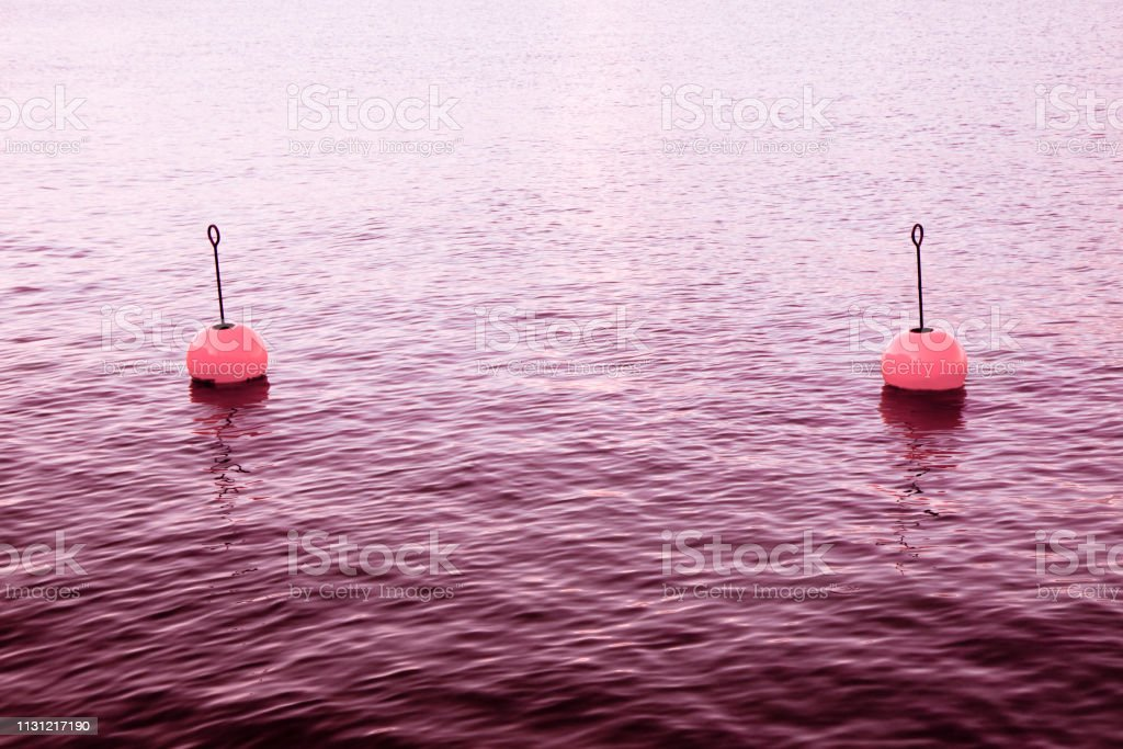 Red bouy on a calm lake - toned image with copy space stock photo
