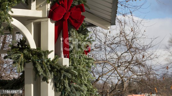 istock Red Bow on a holiday garland under Gazebo 1194499718