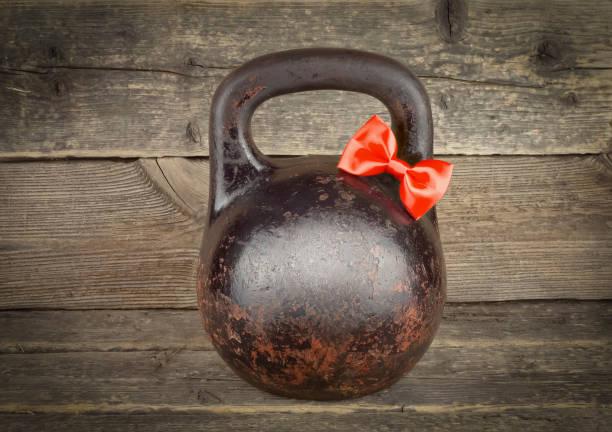 lazo rojo en viejo oxidado kettlebell sobre mesa de madera - boss's day fotografías e imágenes de stock