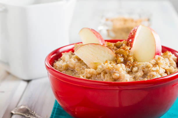 Red Bowl Of Hot Oatmeal With Blueberries and Apple Slices stock photo