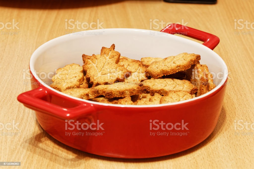 Red bowl with homemade crunchy cookies in the form of leaves stock photo