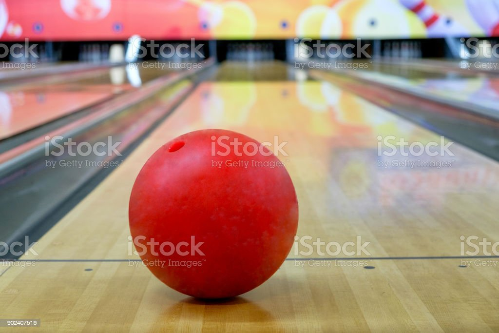 Red bowling ball put on wood alley with blurred bowling pin stock photo