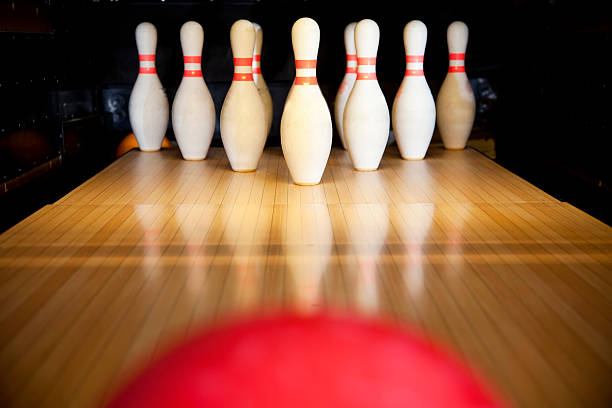 A red bowling ball rolling towards ten upright bowling pins stock photo