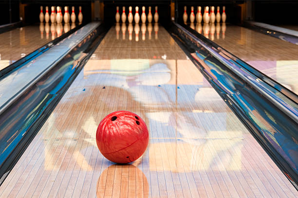 Red bowling ball sitting in middle of newly oiled lane stock photo