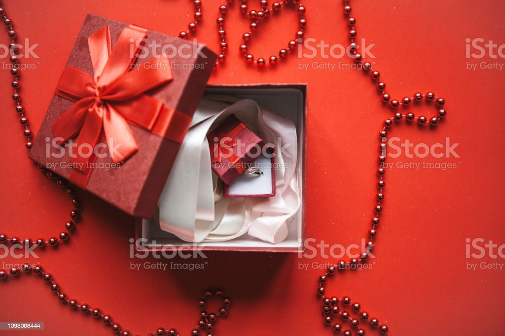 Red box and inside it is another small box with a ring. Concept for...