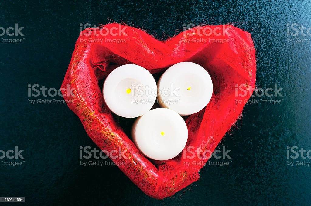 Red box in heart shape and three burning white candles royalty-free stock photo