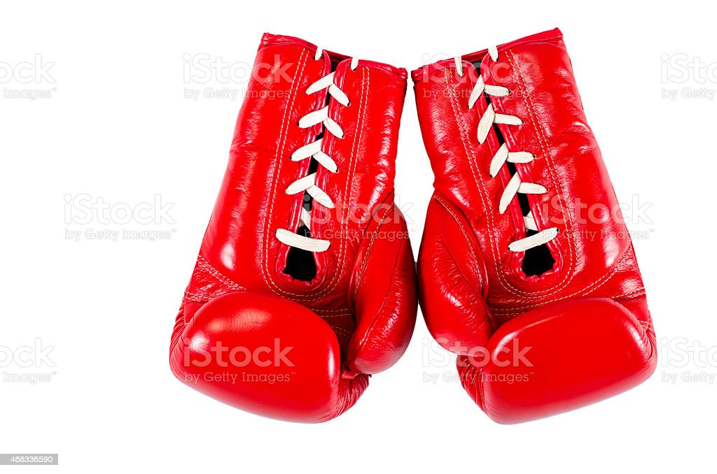 Red boxing gloves pending from a gray wall stock photo