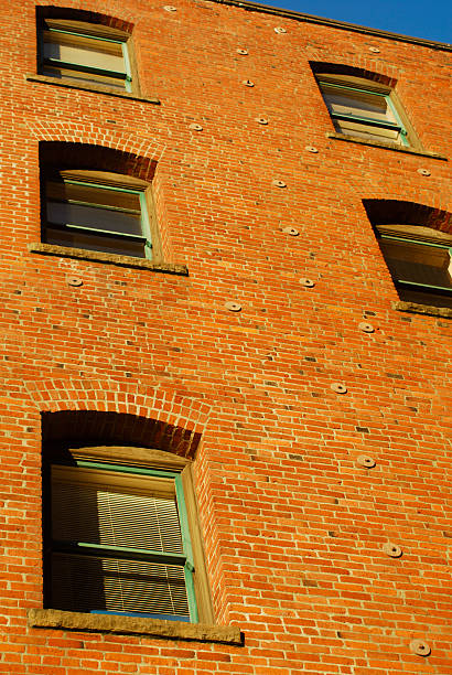 red brick apartment building full of windows stock photo