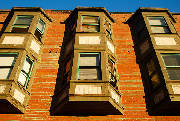 red brick apartment building with blue sky stock photo