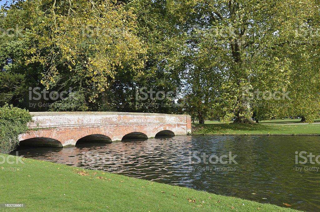 Red brick bridge in formal garden stock photo