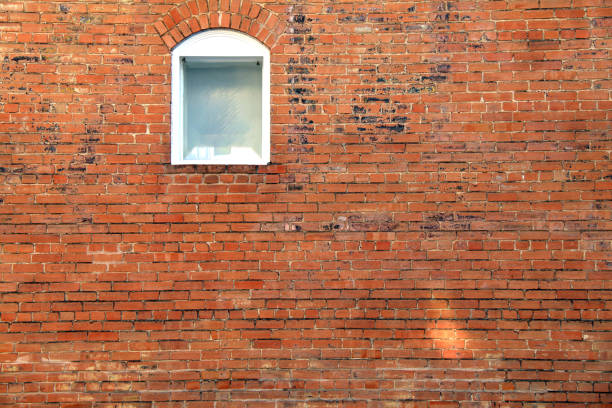 red brick building wall single white arched window