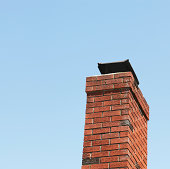 A red brick chimney - with a capped metal grate on top to prevent rain, birds and pests from entering - against a blue sky. Square composition.
